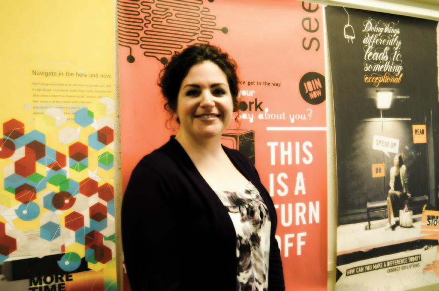 Professor Wendy Shapiro stands in front of posters of her own work, setting an example for students seeking careers in the graphic design field. | Dustin Michelson, staff photographer