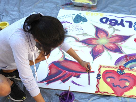 A student makes a poster for a Love Your Body Day event in 2013. File photo