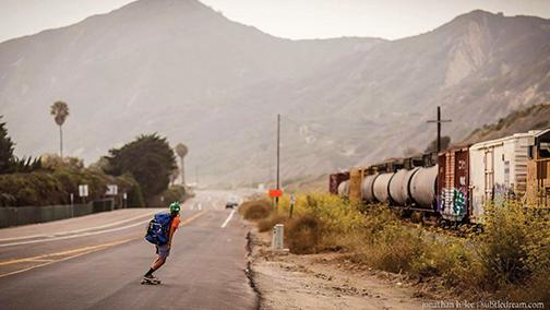 Jin Salamck skateboards the coast of California past a train.