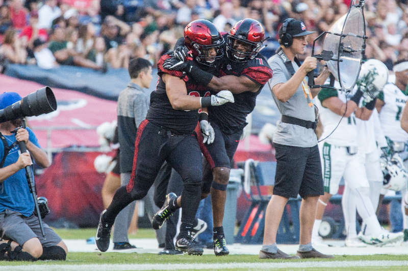 Sophomore linebacker Ronley Lakalaka (39) and junior safety Kameron Kelly (7) celebrate after Lakalaka's interception.