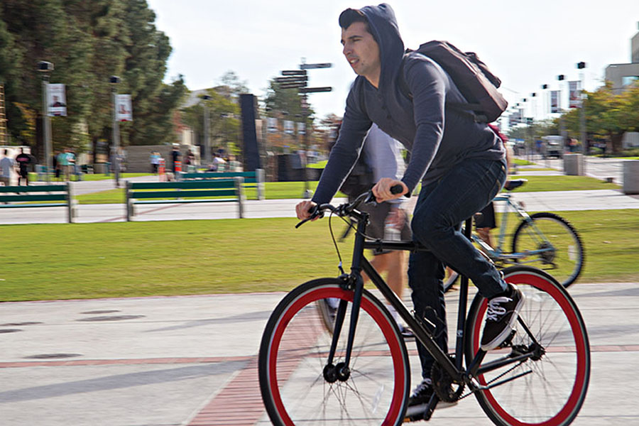 An SDSU student pedals across campus