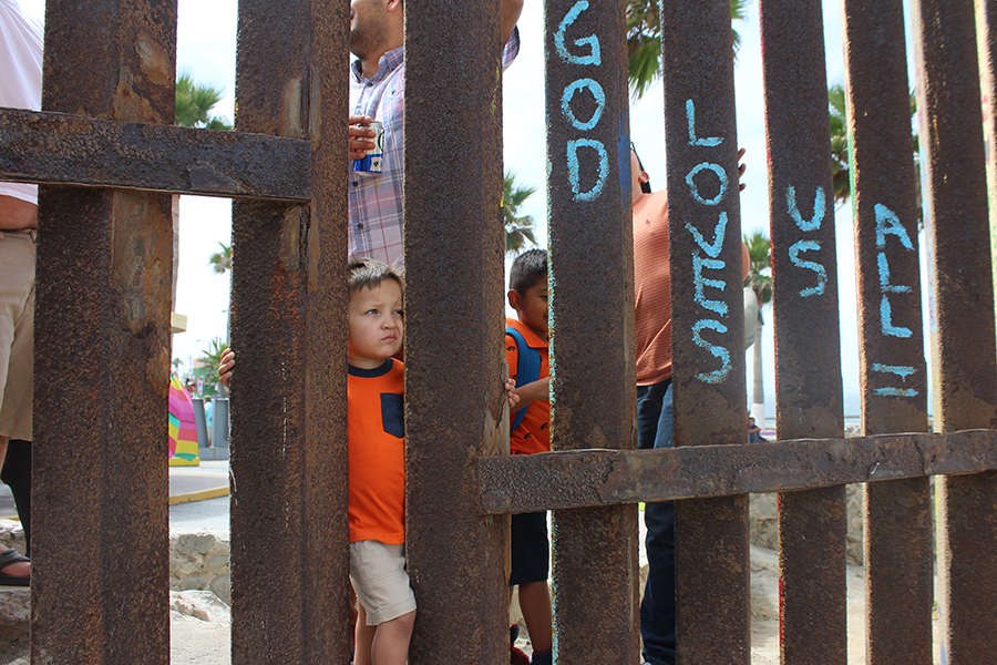 A+child+standing+in+Tijuana+peers+through+the+border+fence+at+Friendship+Park.