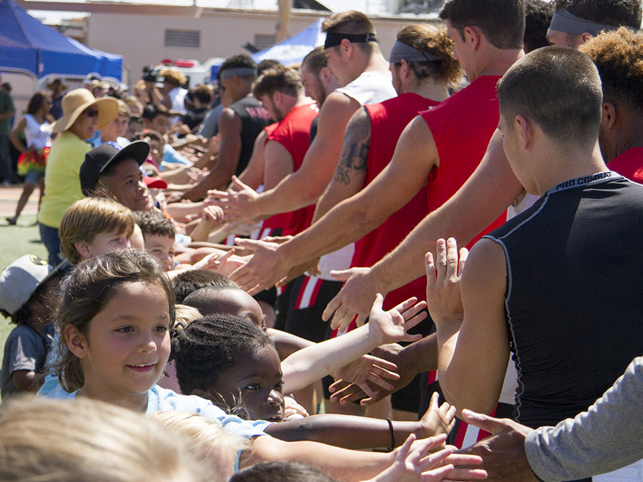 Aztec+football+players+high-five+children+at+their+military+appreciation+event+at+MCAS+Miramar.