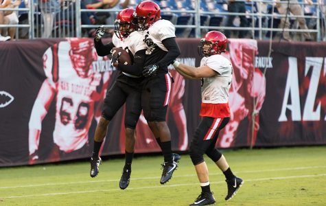 Three Aztec players celebrate after a touchdown by sophomore safety Jeff Clay during Fan Fest.