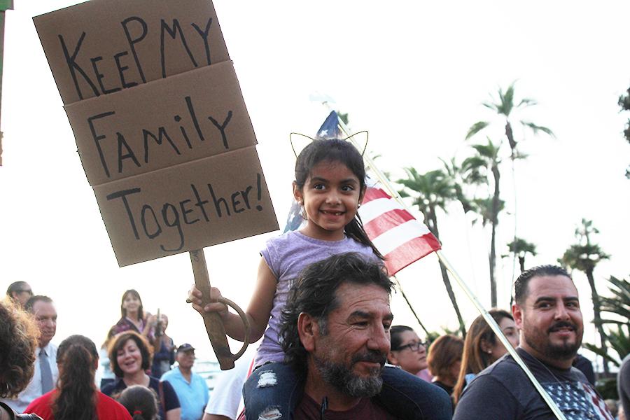 Elizabeth Vega se sienta en los hombros de su abuelo Israel Vega mientras levanta un cartel que lee