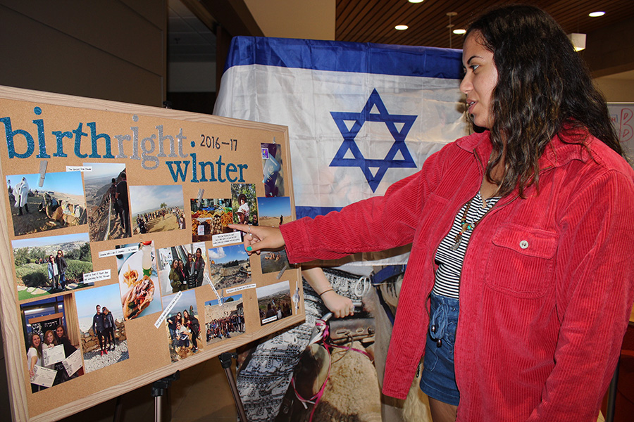 Lauren+Gutin%2C+Students+Supporting+Israel+president%2C+reads+a+poster+in+the+Hillel+Center+detailing+a+birthright+trip.