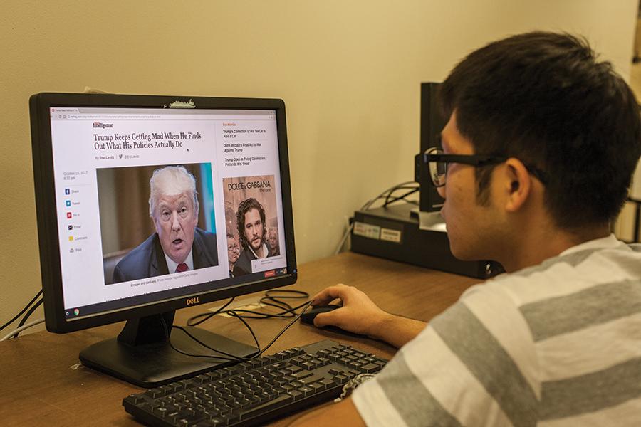 International student Yunjun Yang reads an article about President Donald Trump