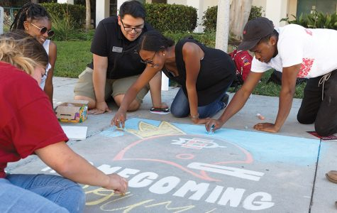 "SDSU students Cha Cha Rane, Abel Mercado, Kimberly Alli and Victor Uwakwe take part in the ""chalking"" homecoming event at the Cal Coast Credit Union Open Air Theatre Oct. 16."