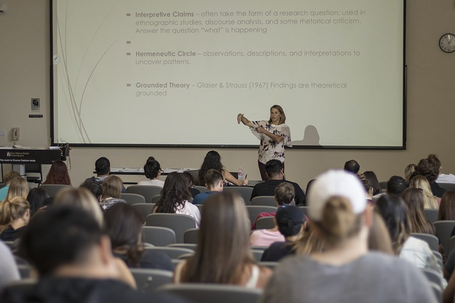 Students listen to a professor in a large lecture class.