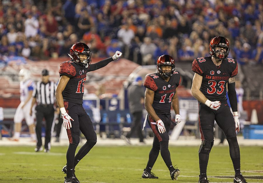 Ron Smith (17), Tariq Thompson (14), and Parker Baldwin (73) celebrate a defensive stop in their game against Boise State on Oct. 14 at SDCCU Stadium. The Aztecs lost the game 31-14.