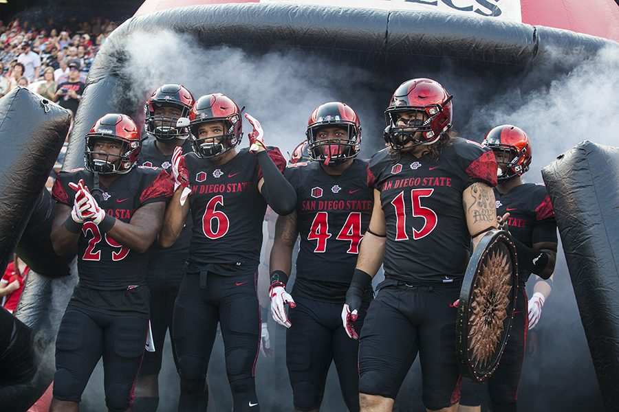 Sophomore+running+back+Juwan+Washington%2C+senior+wide+receiver+Mikah+Holder%2C+sophomore+linebacker+Kyavha+Tezino+and+senior+fullback+Nick+Bawden+lead+SDSU+onto+the+field+before+its+opening+game+win+over+UC+Davis+Sept.+2.