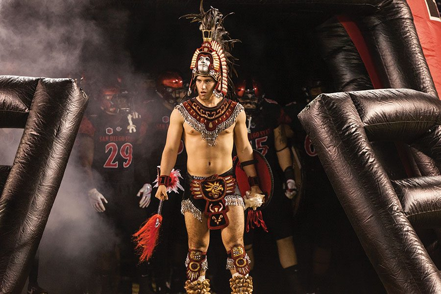 The Aztec Warrior mascot leads the football team on to the field.