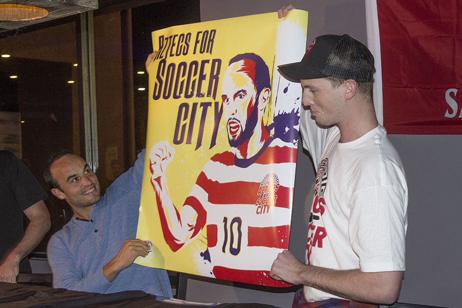 Retired professional soccer player Landon Donovan and graphic design sophomore Chandler Brunelli hold up a poster promoting Aztecs for SoccerCity.