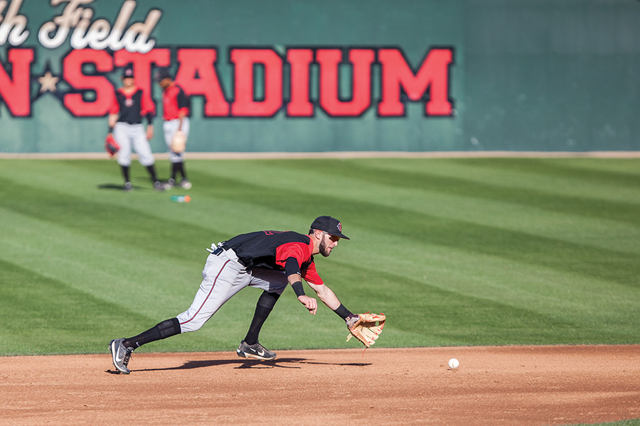 Aztecs junior infielder David Hensley goes for a ground ball during baseball practice on Jan. 26.
