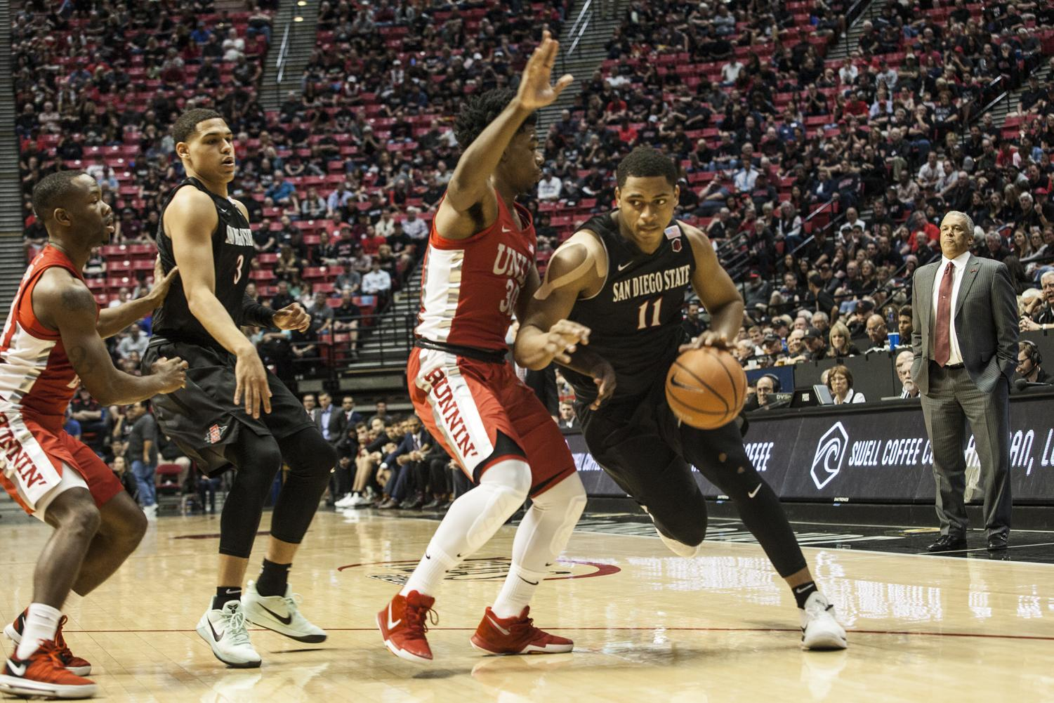 Matt Mitchell drives around UNLV's Jovan Mooring during the Aztecs 94-56 victory on Feb. 17 at Viejas Arena.
