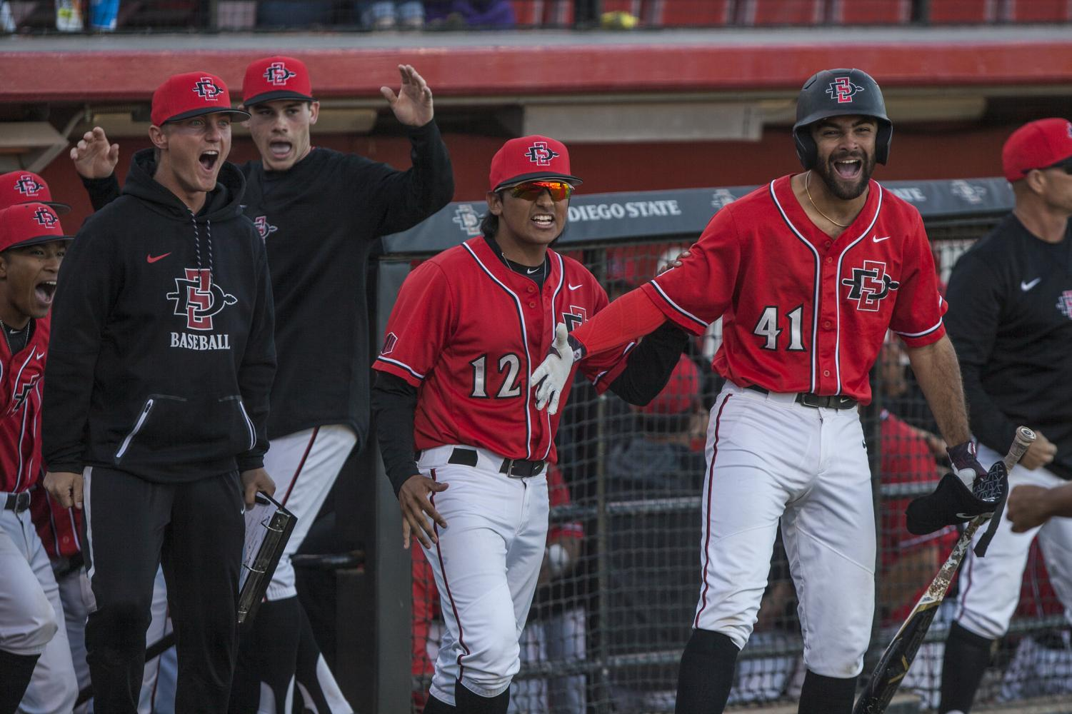 SDSU players celebrated outside the dugout amidst a four-run eighth inning during the Aztecs 5-4 win over Grand Canyon on Feb. 25 at Tony Gwynn Stadium.