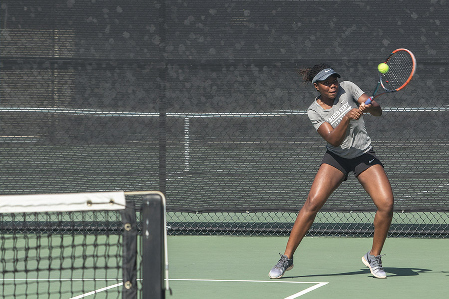 Freshman Nnena Nadozie hits the ball during a home doubles match against USD on Feb. 11. The Aztecs lost the overall match by a score of 4-2.