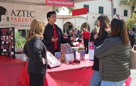 Prospective SDSU students talk to a representative at the Aztec Parents Group table at a previous Explore SDSU event.