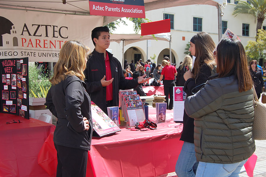 Prospective SDSU students talk to a representative at the Aztec Parents Group table at Explore SDSU on Saturday. Many prospective students haven't yet received acceptance letters.