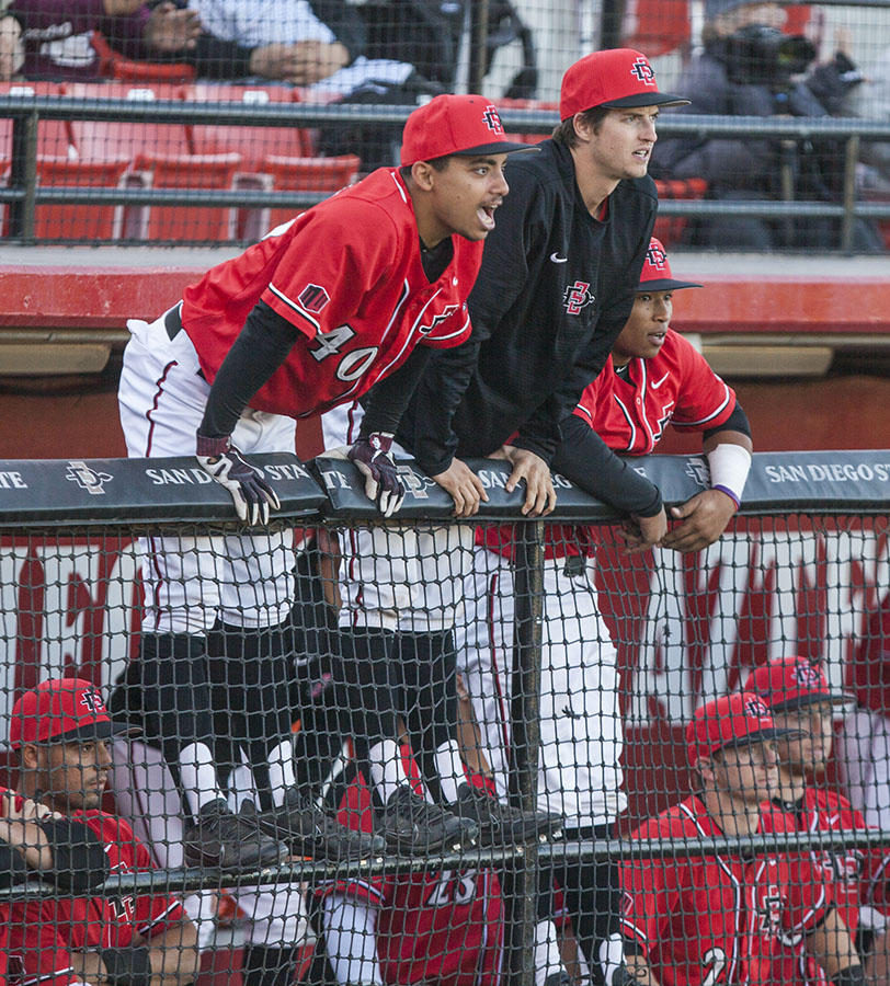 Freshman outfielder Sean Ross and junior pitcher Garrett Hill hang over the dugout railing during the Aztecs 5-4 win over Grand Canyon on Feb. 25 at Tony Gwynn Stadium.