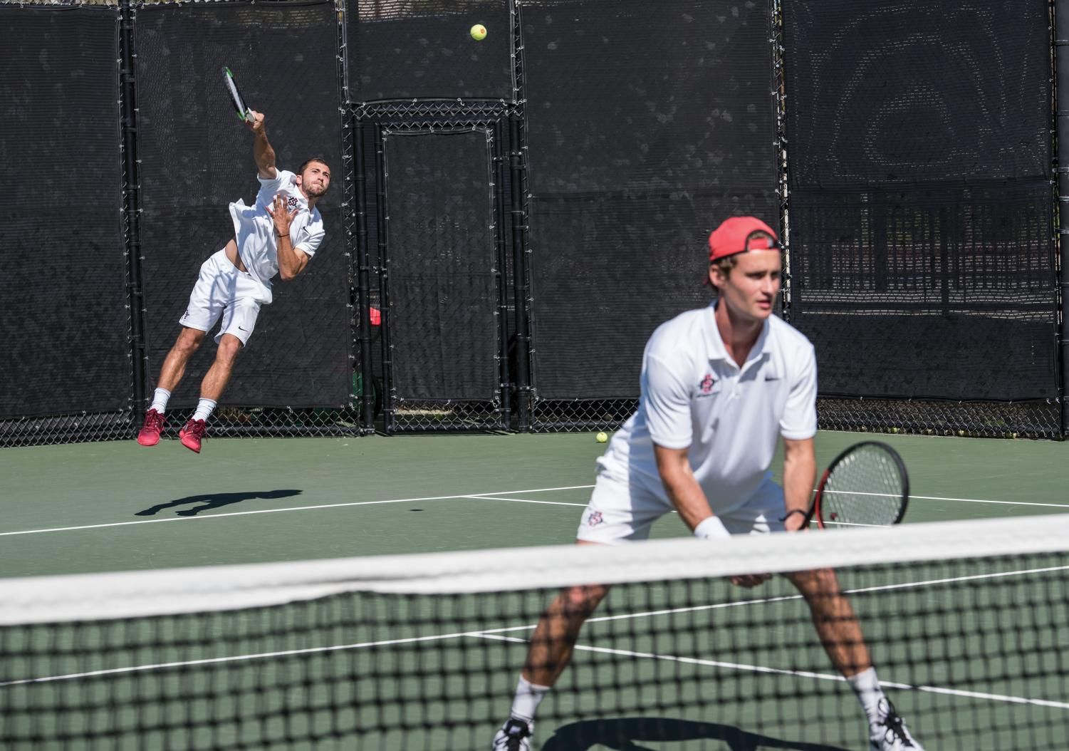Junior Sander Gjoels-Andersen (front) and sophomore Nicholas Mitchell compete in doubles against Cal on March 1 at the Aztec Tennis Center. The match was suspended with Cal winning 4-3.