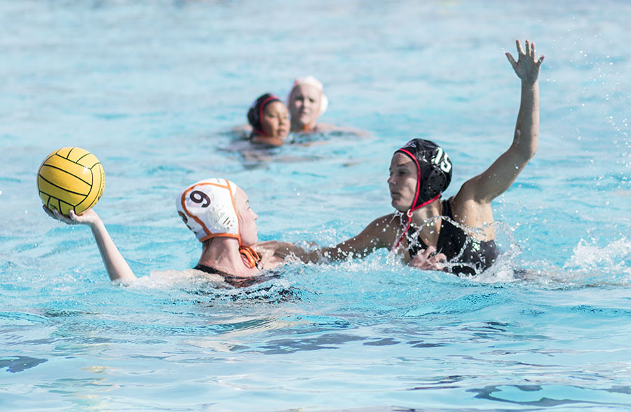 Princeton freshman attacker Kailie McGeoy holds up the ball as senior driver Katrina King defends during the Aztecs 10-4 loss at the Aztec Aquaplex on March 19.