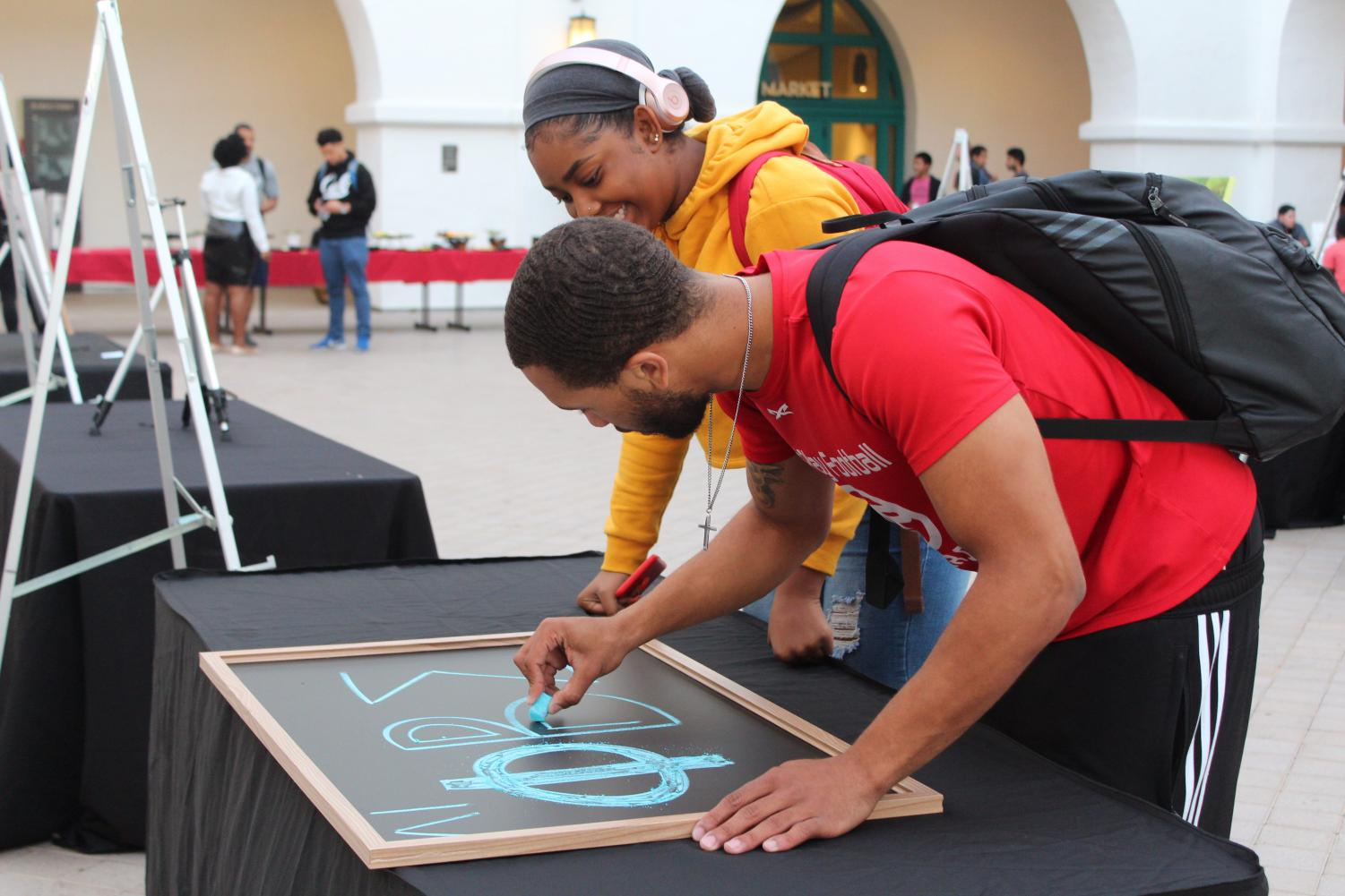 Students at the Aztec Art Contest admire the work.