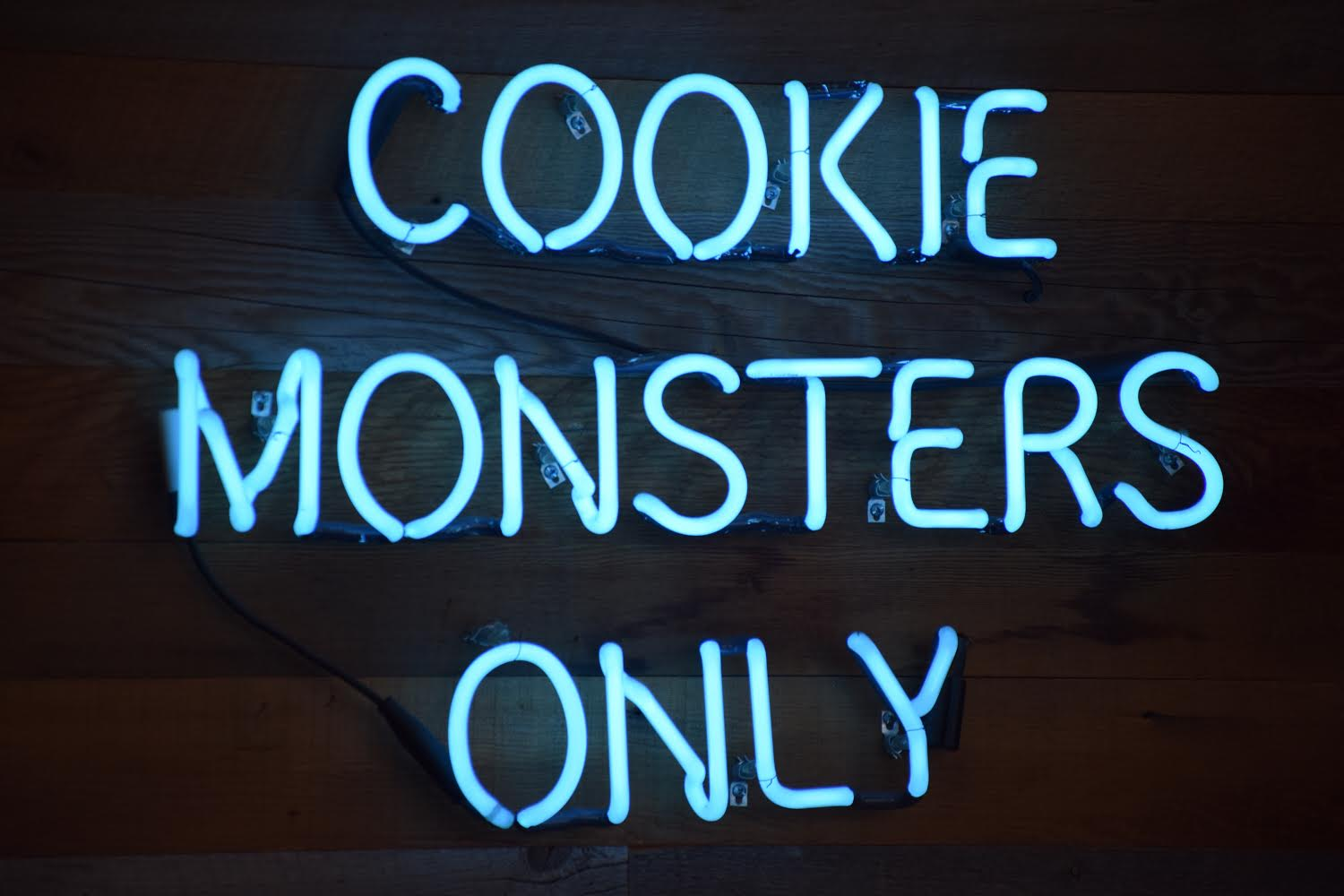 "A blue neon sign welcomes ""Cookie Monsters"" at the Baked Bear in Pacific Beach, where customers come in to design custom ice cream sandwiches."