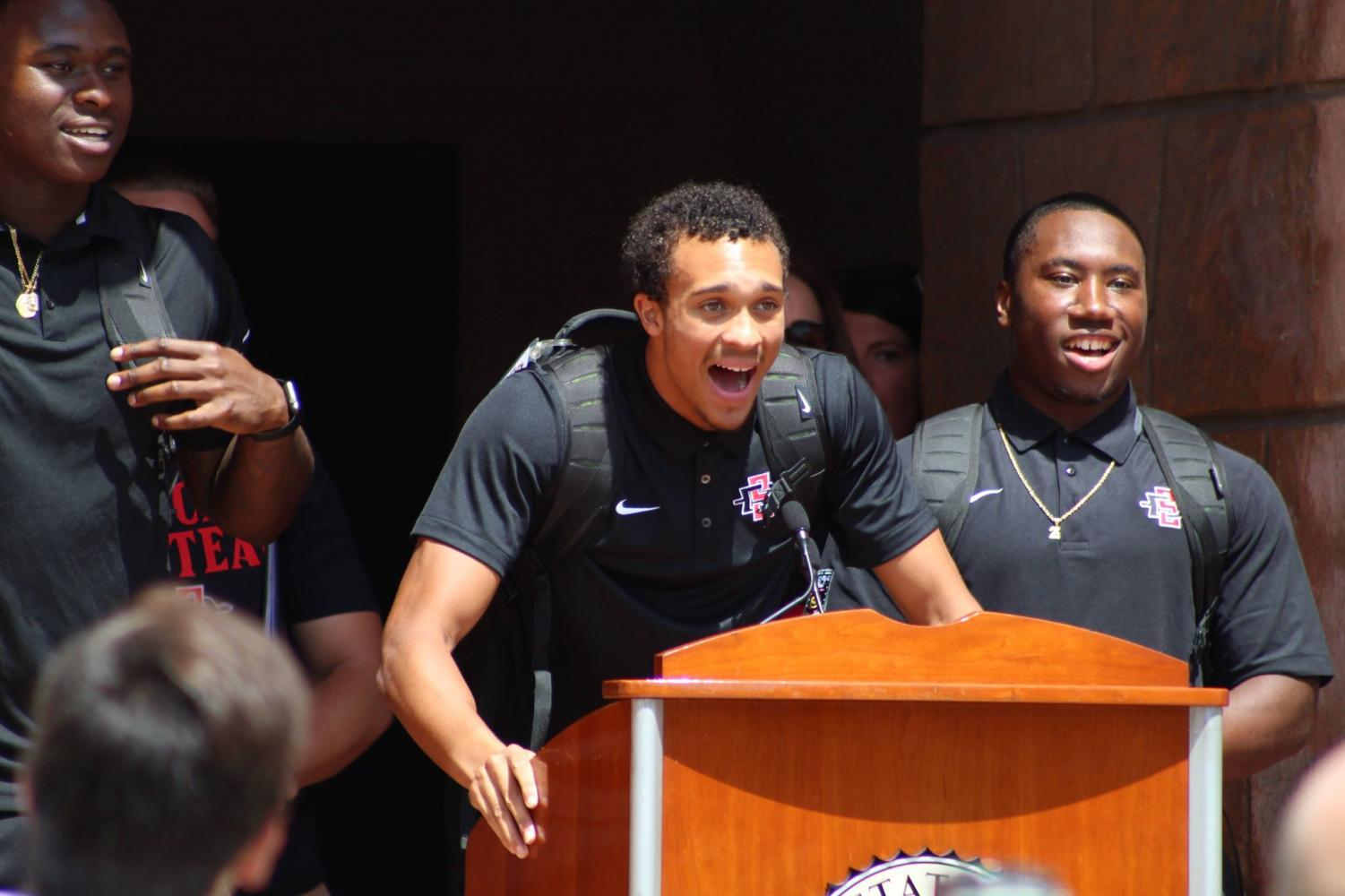 Aztecs cornerback Ron Smith (center) leads the