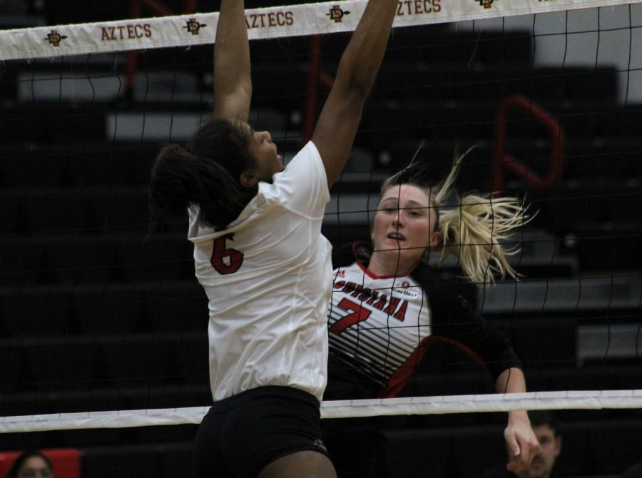 SDSU junior outside hitter Ashlynn Dunbar attempts to block a spike attempt while Louisiana senior outside hitter Hanna Rovira looks through the net during the Aztecs five-set loss to the Ragin' Cajuns on Sept. 15 at Peterson Gym.