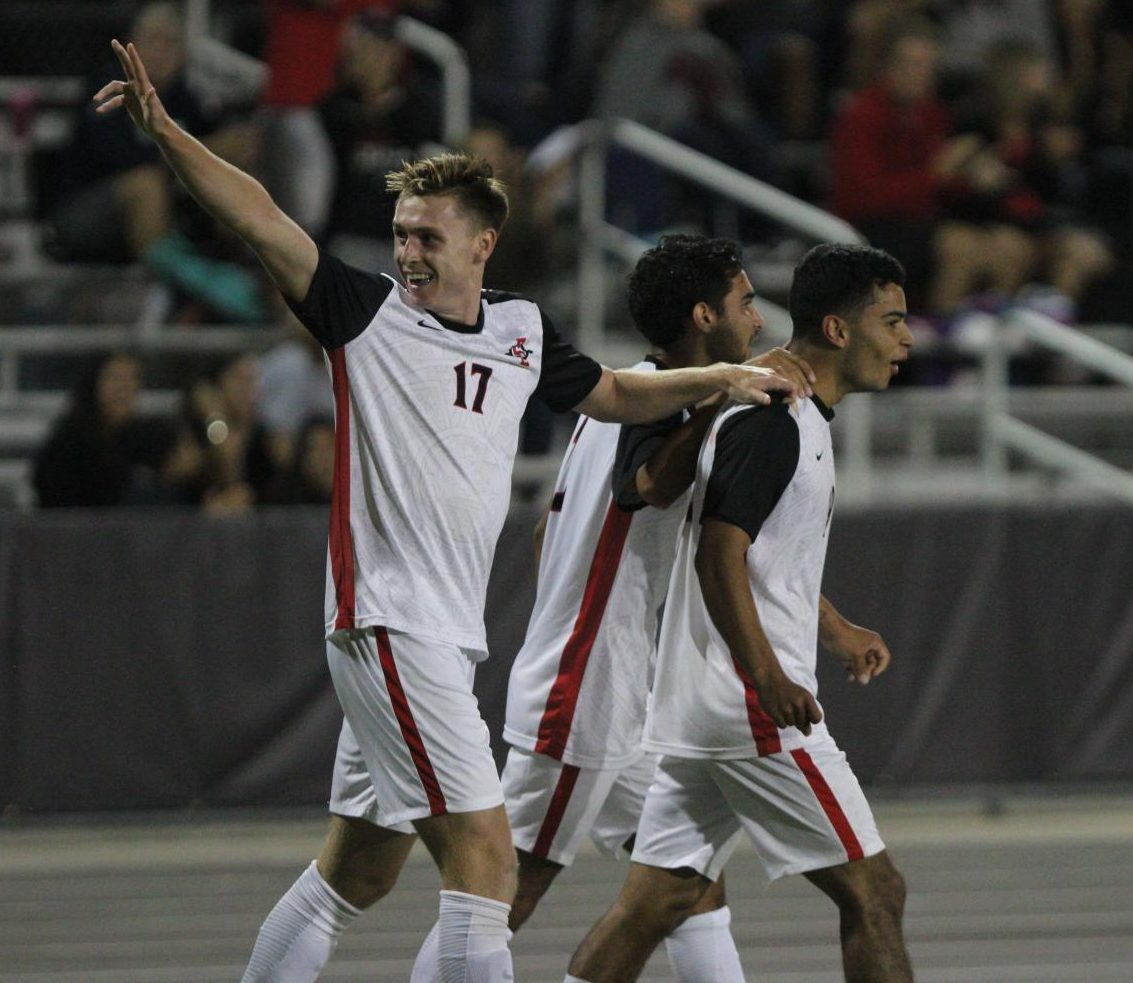 Redshirt-freshman midfielder Reagan Sherlock (left) celebrates with junior midfielder Spencer Madden (middle) and senior forward Damian German (right) during the Aztecs 2-0 victory over Brown on Sept. 15 at the SDSU Sports Deck. German had two goals during the match.