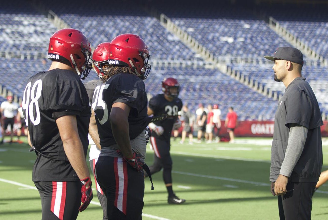 SDSU senior defensive lineman Damon Moore (left), senior defensive lineman Noble Hall (middle) and defensive line coach Ernie Lawson (right) prepare for scrimmage at the annual Fan Fest on Aug. 18 at SDCCU Stadium.