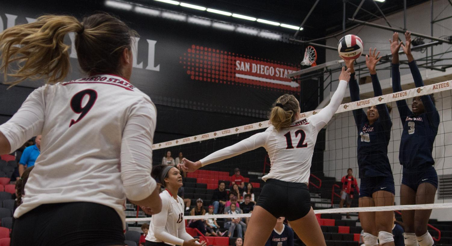 Sophomore middle blocker Erin Gillcrist attempts to get the ball over the outsretched arms of Fresno State defenders during the Aztecs three-set loss  to the Bulldogs on Sept. 21 at Peterson Gym.