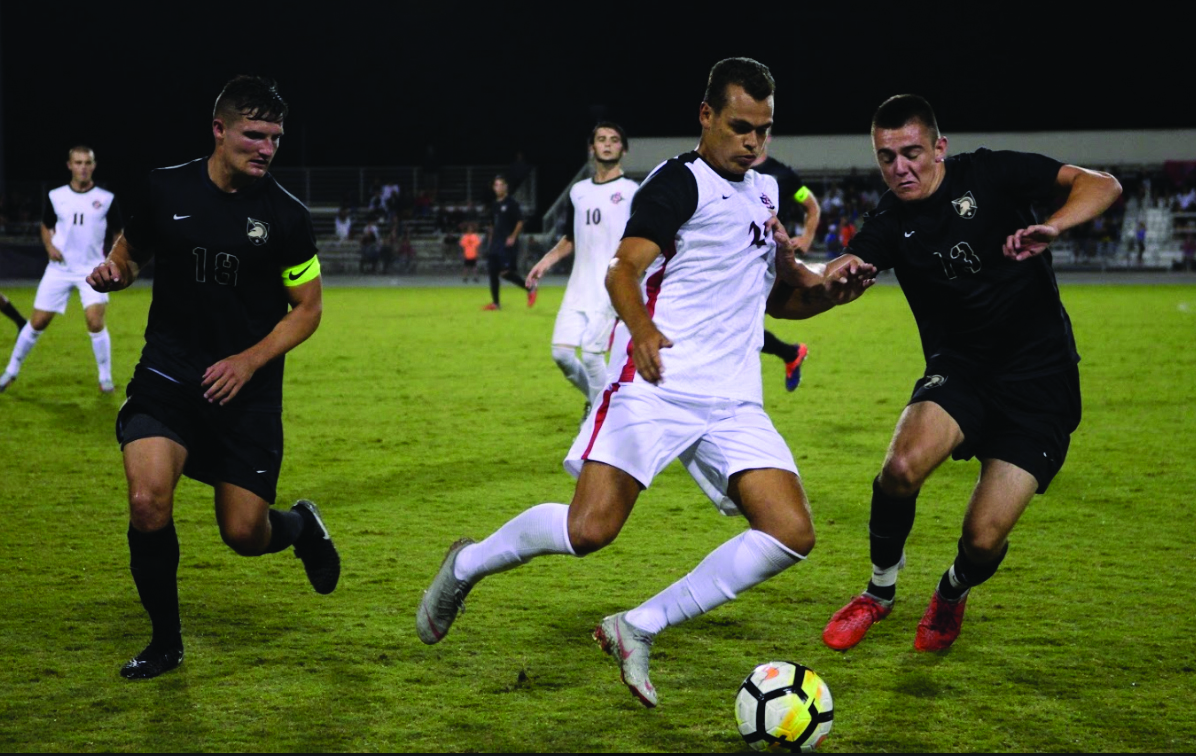 Sophomore midfielder Tevenn Roux dribbles the ball between two Army players during the Aztecs 2-1 loss to Army on Sept. 1 at the SDSU Sports Deck.