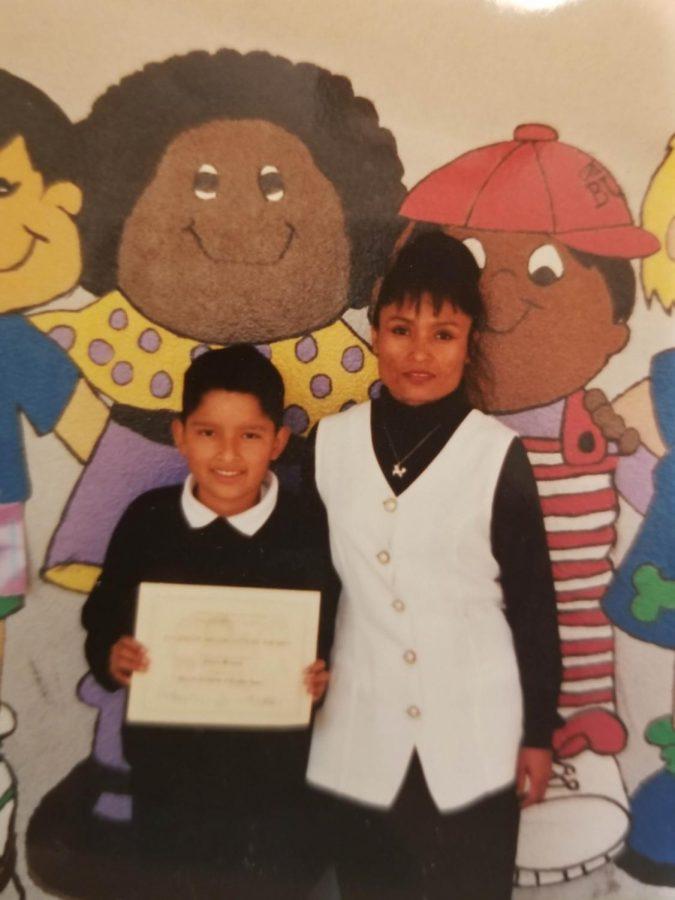 Antonio+M%C3%A1rquez%2C+junto+con+su+mam%C3%A1%2C+recibe+un+diploma+en+la+primaria.