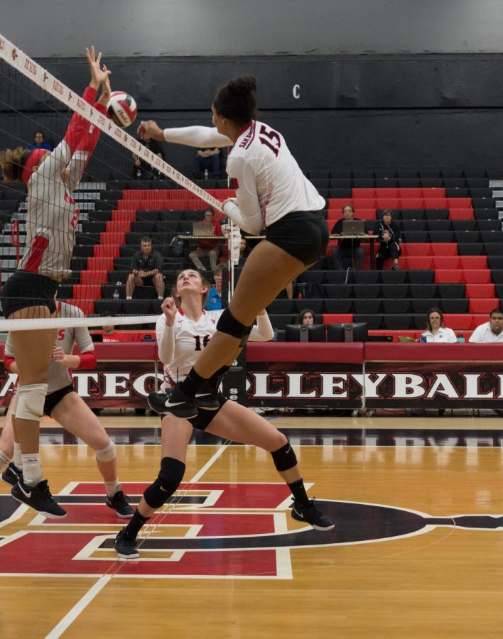 Senior+middle+blocker+Deja+Harris+spikes+the+ball+over+New+Mexico+defenders+during+the+Aztecs+four-set+victory+on+Oct.+11+at+Peterson+Gym.