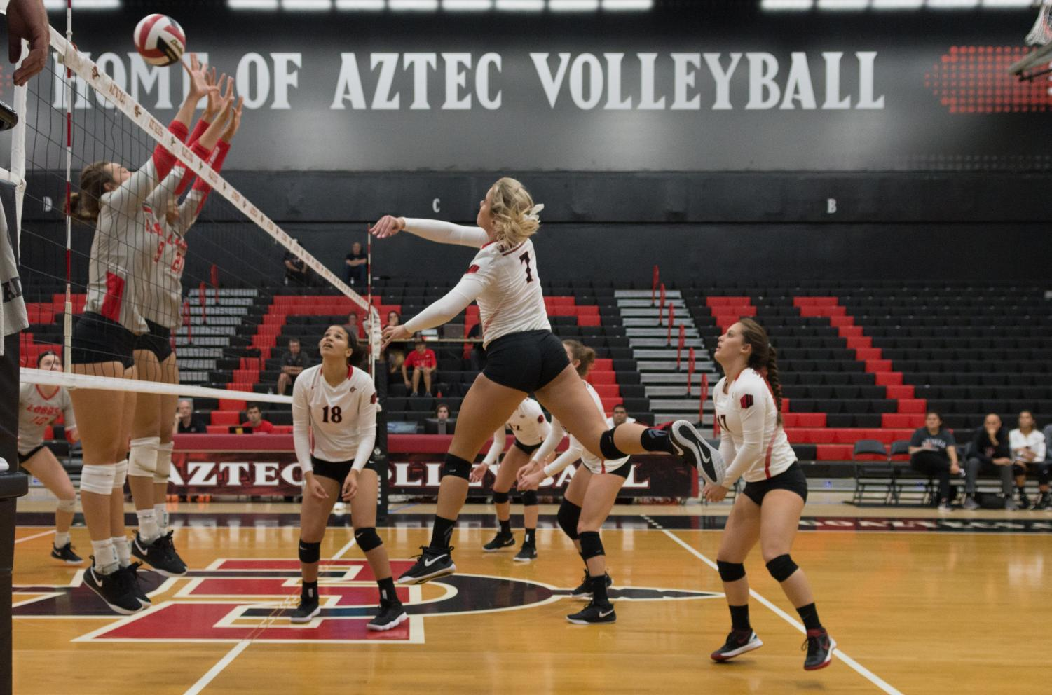 Junior outside hitter Hannah Turnlund spikes a ball over the outstretched arms of the Lobos defenders during the Aztecs four-set victory on Oct. 11 at Peterson Gym.
