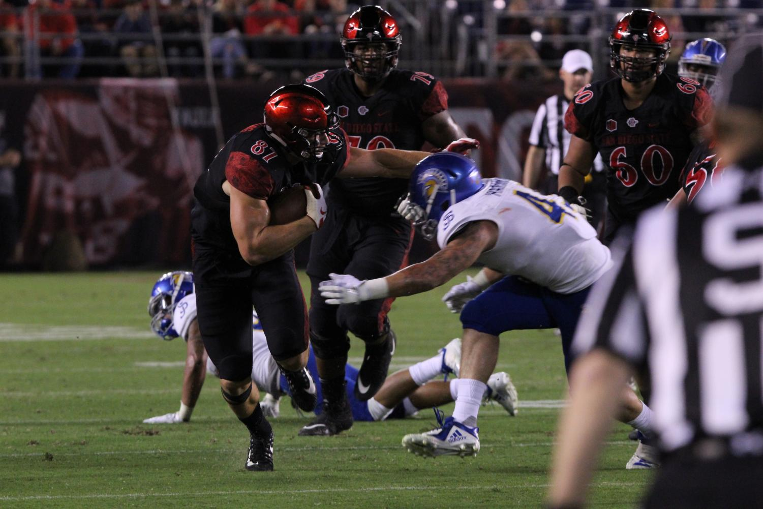 Junior tight end Kahale Warring stiff arms a defender against San Jose State on Oct. 20 at SDCCU Stadium.