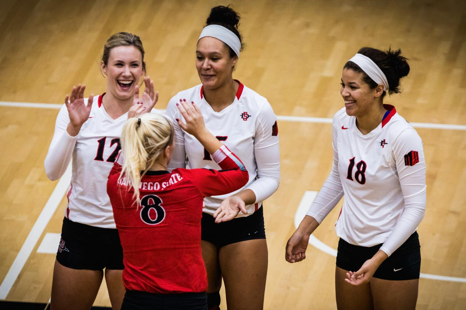 (Left to right) sophomore middle blocker Erin Gilchrist, senior middle blocker Deja Harris and junior middle blocker Tamia Reeves celebrate with redshirt sophomore defensive specialist Loren Teter (front) during the Aztecs three-set victory over Utah State on Nov. 1 at Peterson Gym.