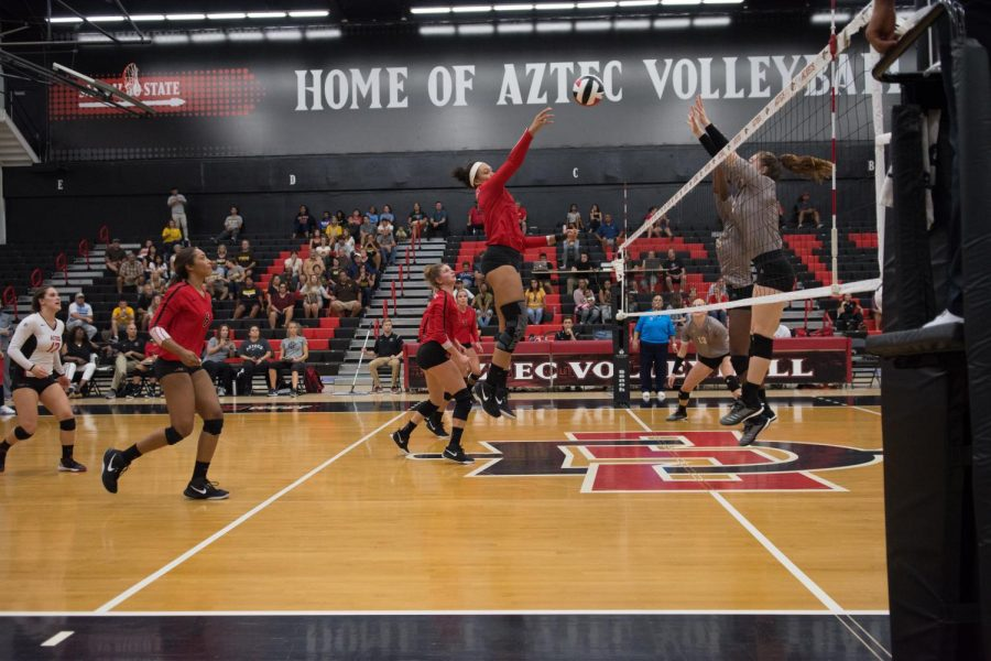 Senior middle blocker Deja Harris attempts to hit the ball over a Wyoming defender on Sept. 29 at Peterson Gym.