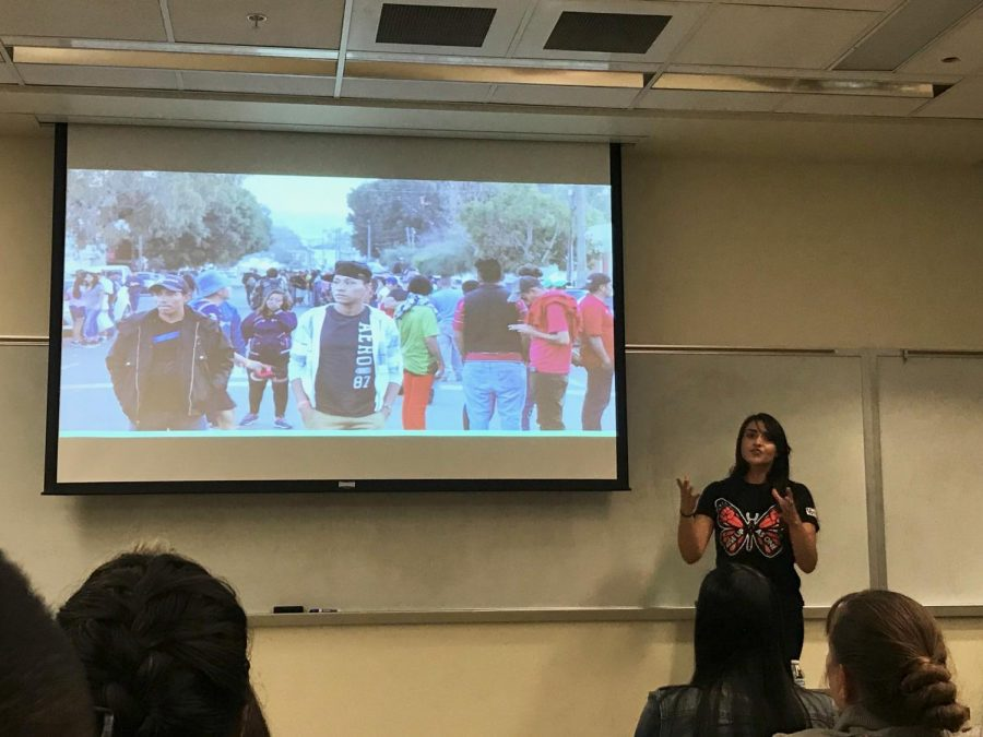 Border Angels Outreach Coordinator Leticia Guzman displays a photo of migrants in Tijuana on their first days in the city to a class at San Diego State on Dec. 10.