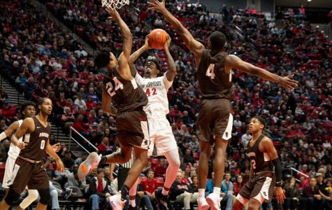 Senior guard Jeremy Hemsley attempts a shot against two Brown defenders during the Aztecs 82-61 loss against the Bears on Dec. 29 at Viejas Arena.
