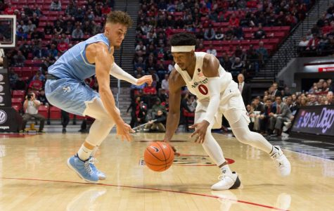 Senior guard Devin Watson (right) scrambles for a loose ball with redshirt senior forward Isaiah Pineiro during the Aztecs 73-61 loss to USD on Dec. 5 at Viejas Arena.