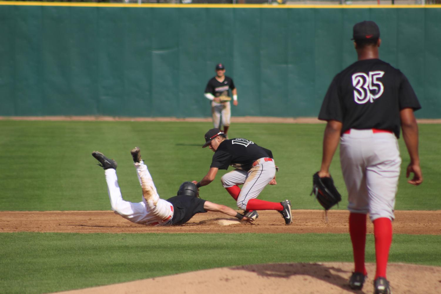 Freshman infielder David Alamillo tags out a member of the SDSU alumni while freshman right hander Aaron Eden looks on. The Aztecs defeated the alumni by a score of 8-2 on Jan. 26 at Tony Gwynn Stadium.