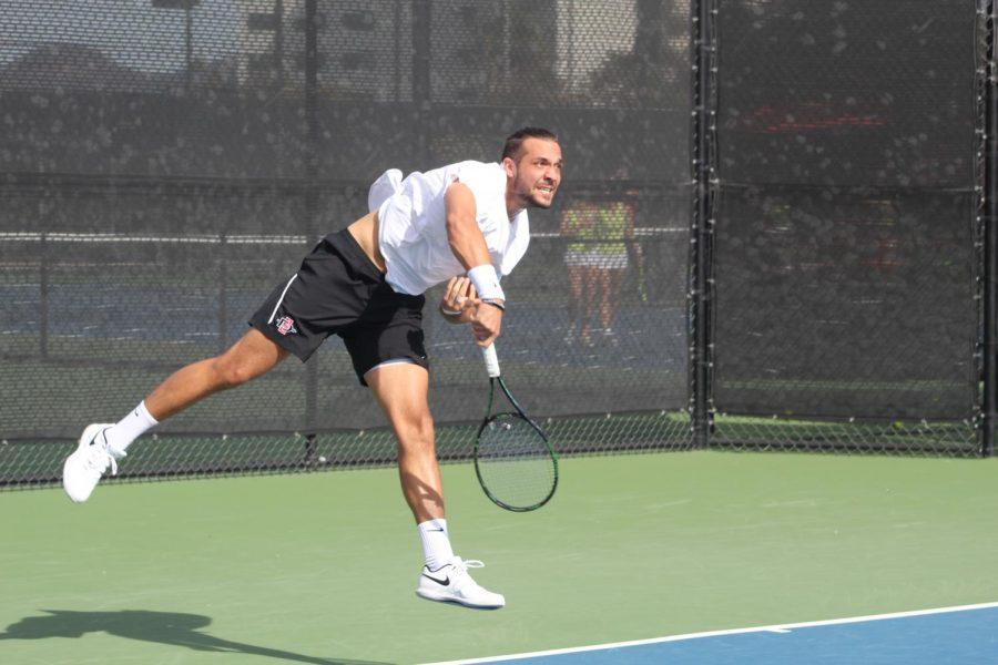 Junior Fabian Roensdorf completes a serve during the Aztecs 5-2 loss against UC Santa Barbara on Jan. 20 at the Aztec Tennis Center.
