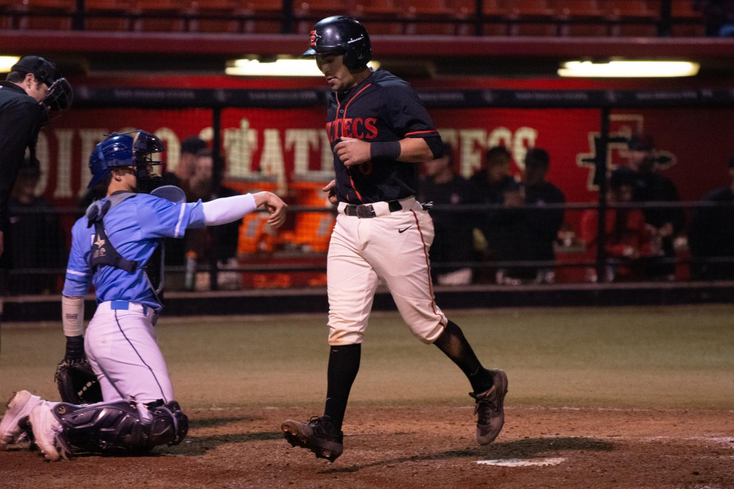 Senior infielder Angelo Armenta steps on home plate to score a run during the Aztecs' 4-2 loss against San Diego on Feb. 23 at Tony Gwynn Stadium.