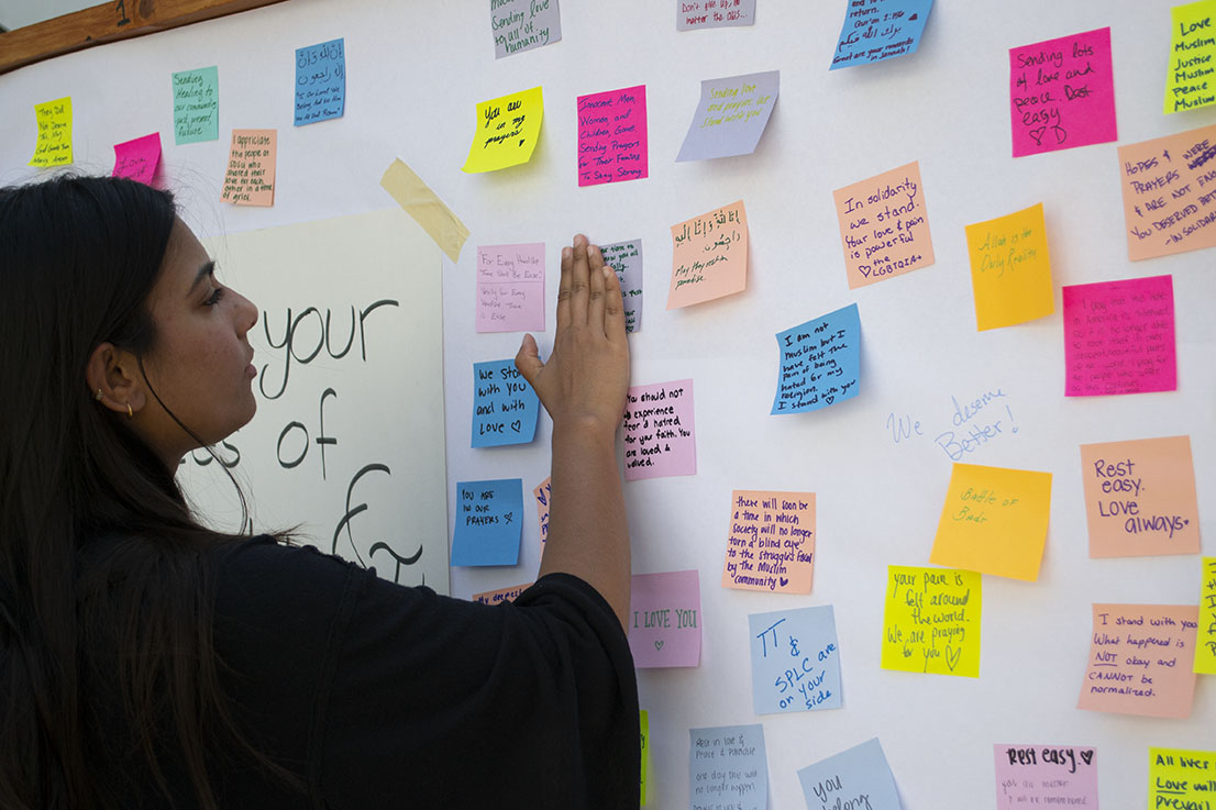 A student placed  post-it with words of support on a wooden board in the student union on March 25.