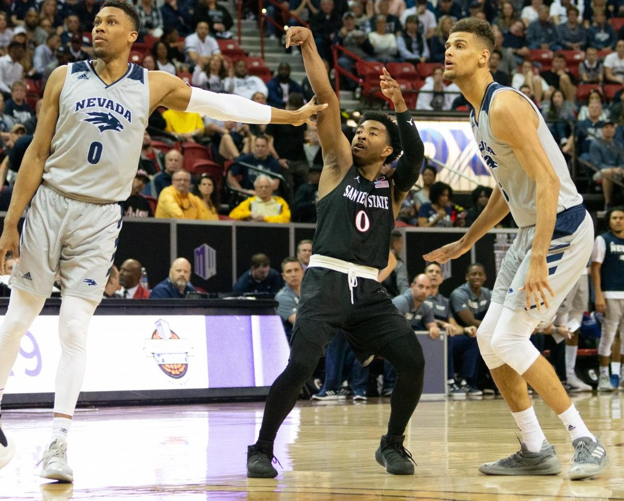 Senior guard Devin Watson launches a 3-pointer over two Nevada defenders during the Aztecs' 65-56 victory on March 16 at the Thomas and Mack Center in Las Vegas.