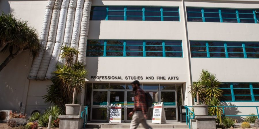 A student passes the College of Professional Studies and Fine Arts building at San Diego State on March 28, 2019. The building was closed from odors because of roofing repairs.