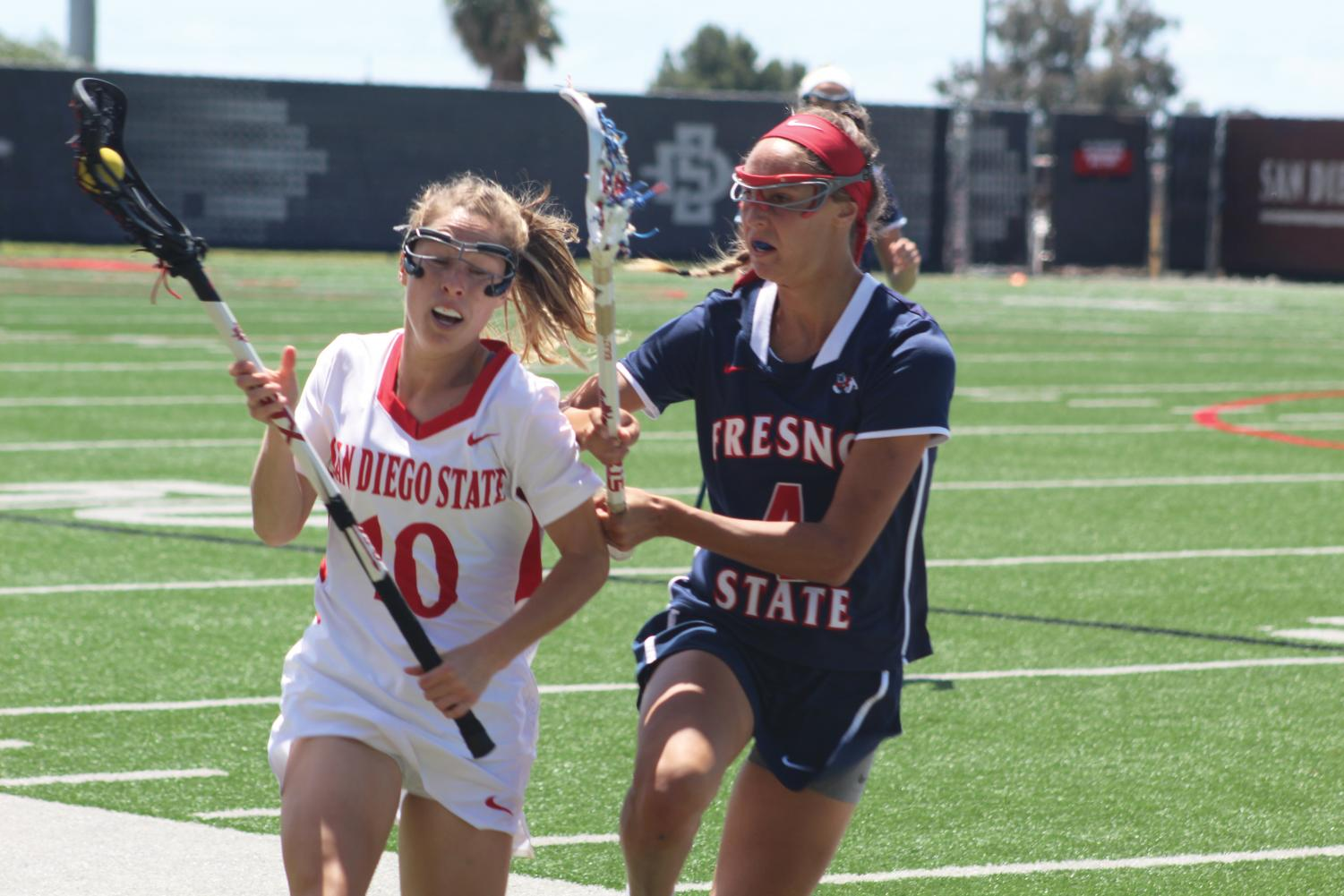 Junior midfielder Marissa Macrae (10) shrugs off Fresno State junior midfielder Kayla Galet (4) during the Aztecs' 16-15 victory over the Bulldogs on April 20 at the SDSU Lacrosse Field.